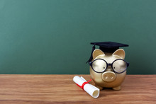 A piggy bank sitting on a wood table with a graduation cap, glasses, and a diploma on its left. There's a green chalkboard behind it.